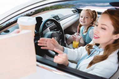 selective focus of smiling businesswoman taking take away order with daughter on passengers seat in car