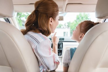 back view of mother showing something to daughter on passengers seat in car
