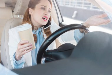 businesswoman with cup of coffee in hand talking on smartphone while driving car