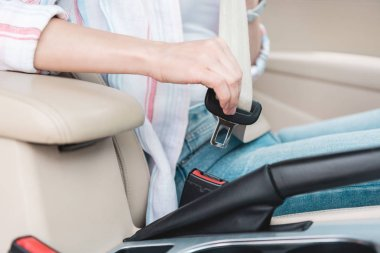 partial view of woman fastening seat belt in car