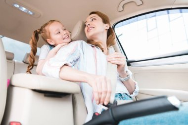 low angle view of woman fastening seat belt while driving car with daughter behind