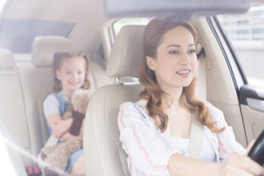 selective focus of smiling mother driving car with daughter on passengers seat behind