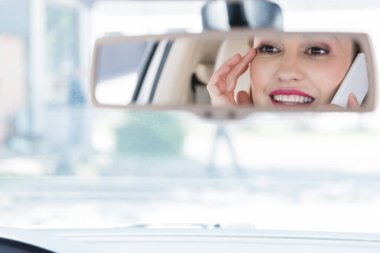partial view of smiling woman talking on smartphone while driving car