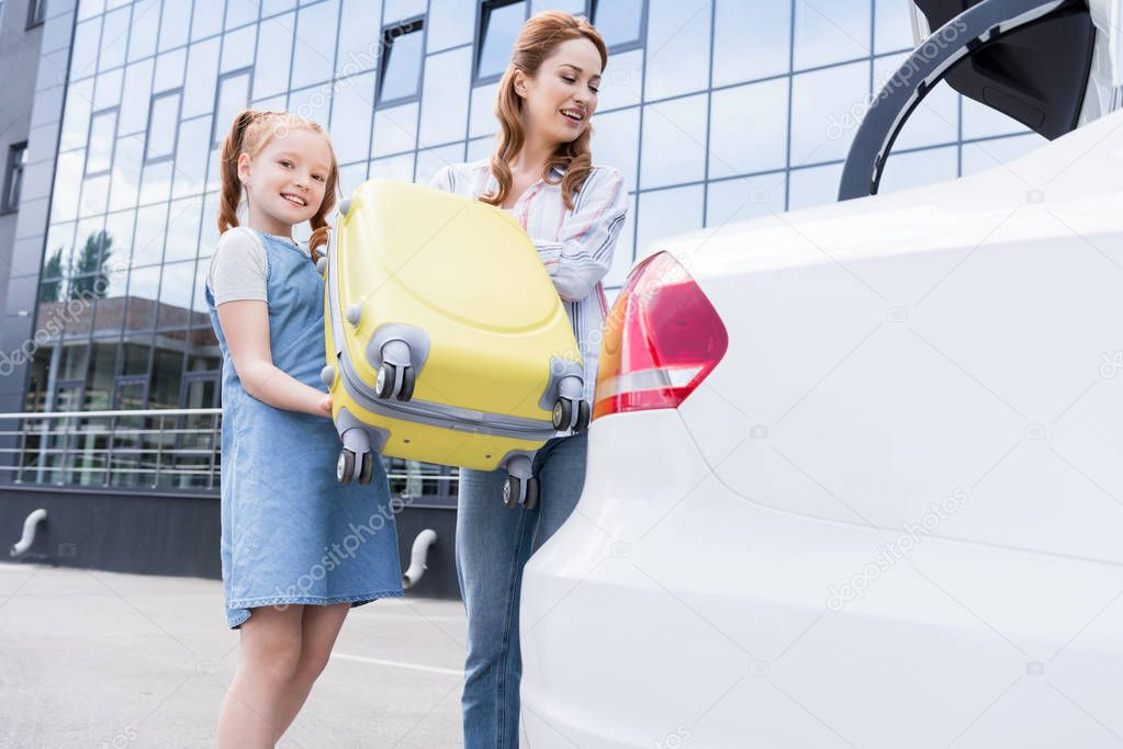 cheerful family putting baggage into car on street