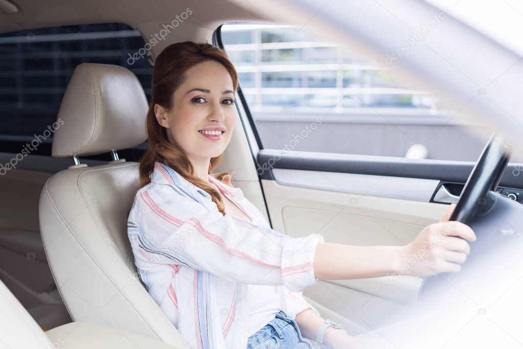 side view of smiling woman looking at camera while driving car