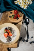 Fotografie Chia seeds in bowl with strawberries and blueberries on wooden board