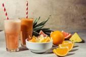 Fotografie Brýle s citrusové šťávy a ovoce kusů na šedý stůl