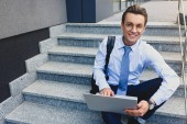 handsome young businessman using laptop and smiling at camera while sitting in stairs