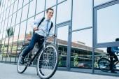 krásný usměvavý mladý muž v brýle a formální oblečení jízdní kolo na ulici