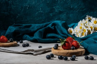 Strawberries and blueberries with tablecloth and daisies on table