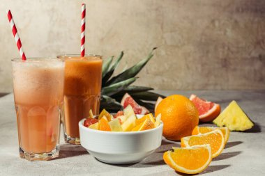 Glasses with citrus juice and fruits pieces on grey table