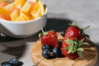 Strawberries and blueberries on wooden board by bowl with citrus fruits