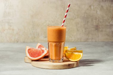 Fresh juice in glass with orange and grapefruit pieces on wooden board