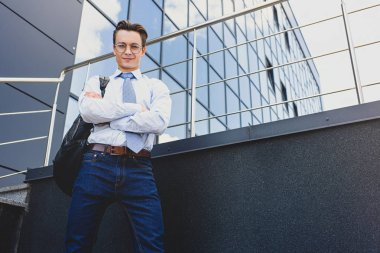 low angle view of handsome young businessman standing with crossed arms and looking at camera outside office building