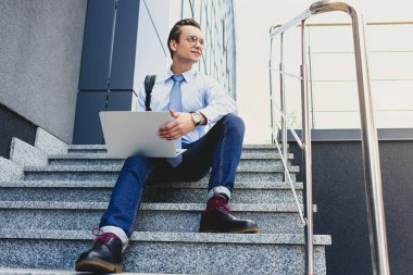 low angle view of handsome young businessman in eyeglasses sitting on stairs and using laptop
