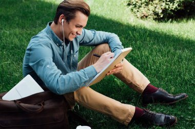 high angle view of smiling young man in earphones taking notes in notepad