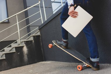 cropped shot of young man holding laptop and riding skateboard