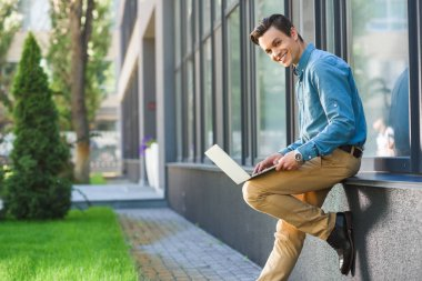 handsome young man using laptop and smiling at camera