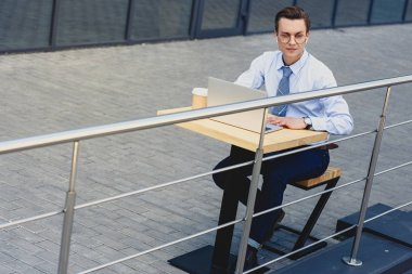 high angle view of young businessman in eyeglasses using laptop outside