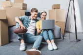Photo beautiful young couple sitting on floor in bedroom of new home and using laptop