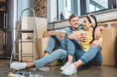 Photo young interracial couple with paper cups of coffee sitting on floor while moving into new home