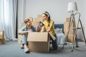 interracial young couple unpacking boxes while moving into new home