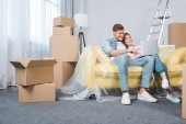 Photo beautiful young couple using laptop together on couch while moving into new home