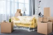 Fotografie prázdnou obývací pokoj s gauči a hromádky polí během přemístění
