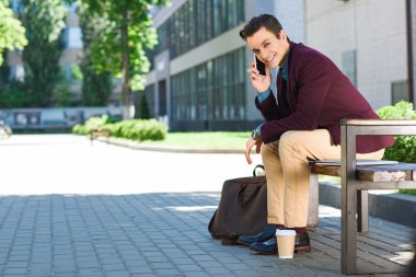 handsome young man talking by smartphone and smiling at camera while sitting on bench