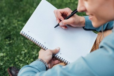 cropped shot of smiling young man writing in blank notebook while sitting on grass