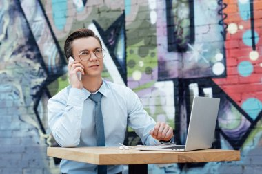 handsome young man in eyeglasses talking by smartphone and using laptop