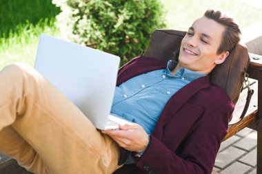 happy young freelancer lying on bench and using laptop
