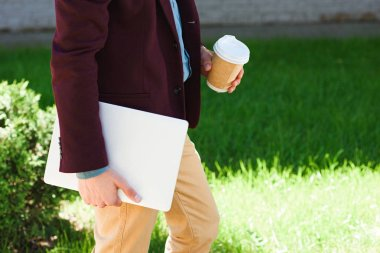 cropped shot of man with laptop and paper cup walking outside
