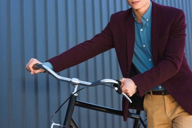 cropped shot of young man standing with bicycle outside