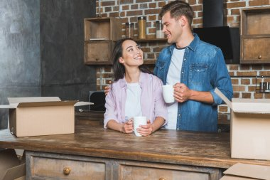 beautiful young couple drinking coffee at kitchen of new home