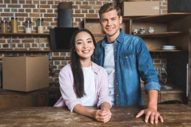 happy young couple standing at kitchen of new home