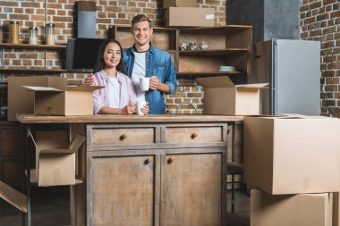 beautiful young couple with mugs of coffee and boxes standing on kitchen during moving into new home