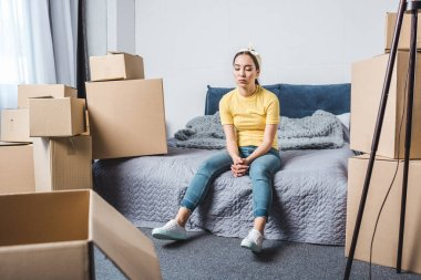 exhausted young woman surrounded with boxes relaxing on bed after relocation