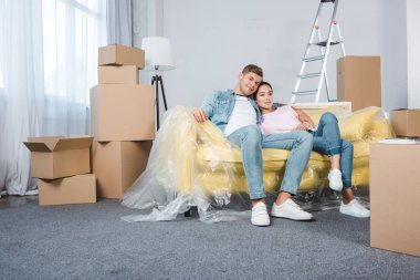 happy young couple relaxing on sofa while moving into new home
