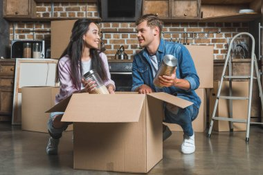 interracial young couple unpacking boxes on kitchen while moving into new home