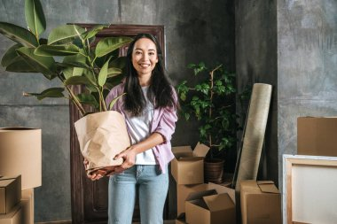 happy young woman with ficus plant and boxes moving into new house