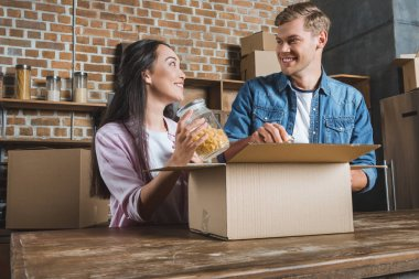 happy young couple unpacking boxes on kitchen while moving into new home