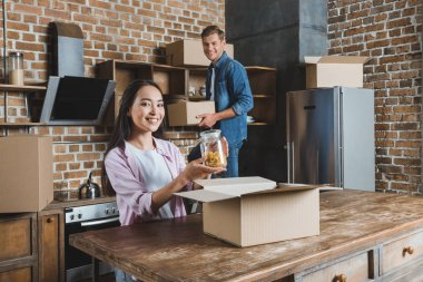 beautiful young couple unpacking boxes on kitchen while moving into new home