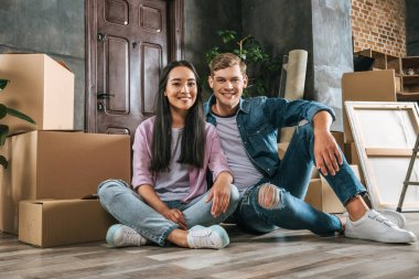 attractive young couple sitting on floor together while moving into new home