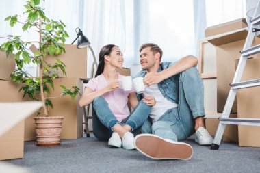 smiling young couple sitting on floor together and clinking mugs with coffee while moving into new home