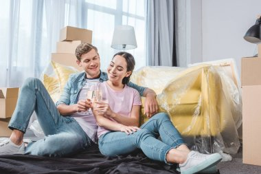 beautiful young couple clinking glasses of champagne while sitting on floor at new home