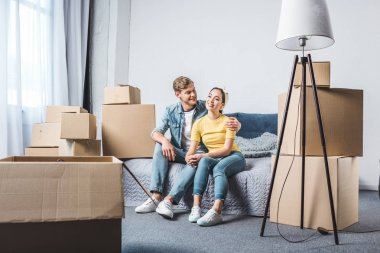 beautiful young couple sitting on bed after moving into new home surrounded with boxes