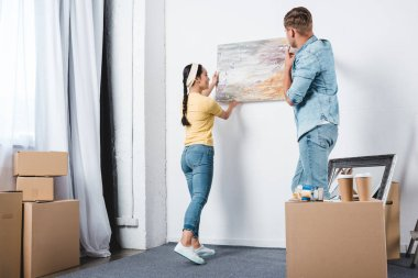 young couple handing abstract picture on wall while moving into new home