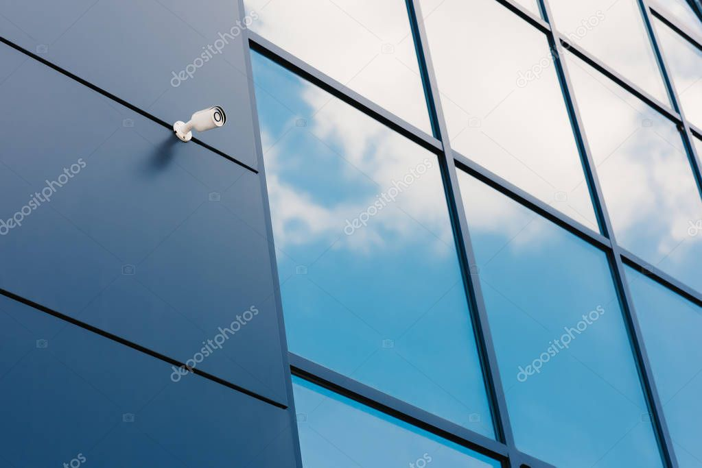 Glass facade of modern office building with security camera and reflected clouds