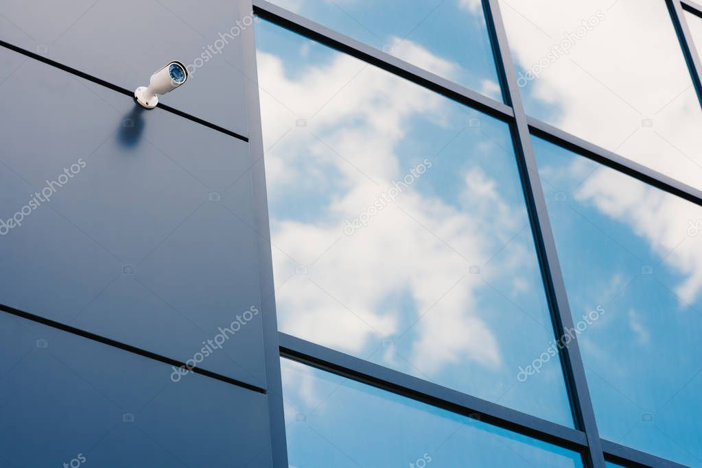 Glass facade of modern office building with security camera